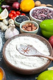 Bovenaanzicht van verse groenten, eieren, citroenbundels, kruiden, gevallen oliefles en bloem in een bruine pot op donker