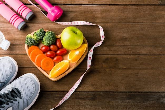 Bovenaanzicht van verse groenten en fruit in hart plaat hout