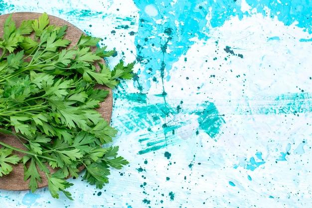 Bovenaanzicht van verse groenten geïsoleerd op bruin houten bureau en helderblauw