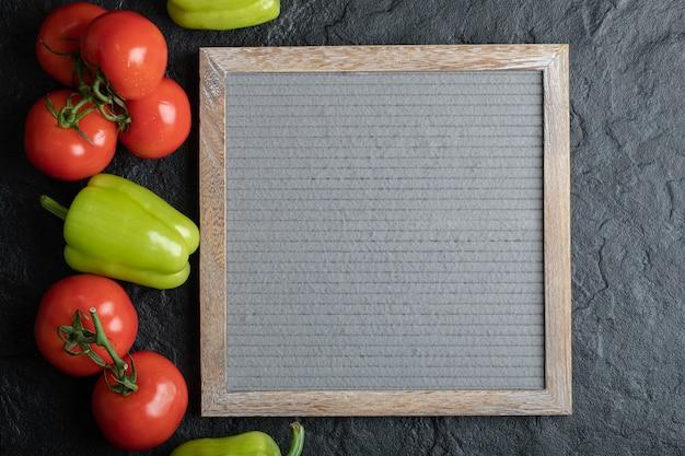 Bovenaanzicht van verse groenten met bord op zwarte achtergrond.