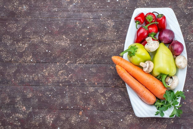 Bovenaanzicht van verse groenten met champignons in plaat op bruin, plantaardig voedsel maaltijd champignons