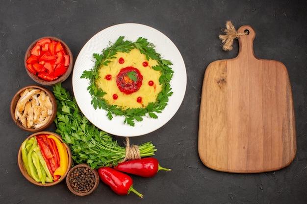 Bovenaanzicht van verse groenten met groenen en aardappelschotel op zwart