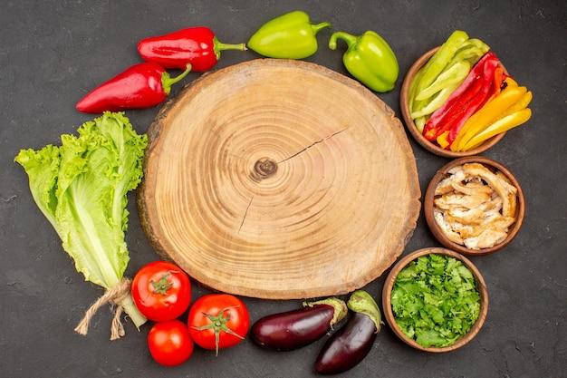 Bovenaanzicht van verse groenten met groenen op zwart