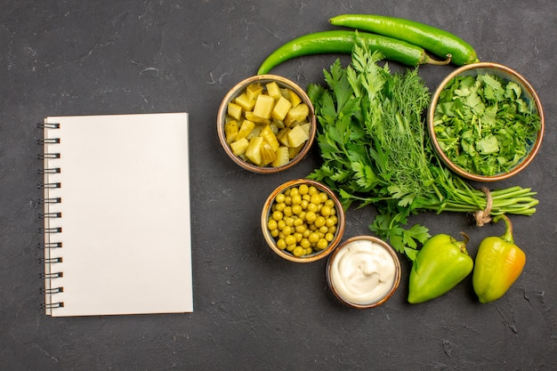 Bovenaanzicht van verse groenten met ingrediënten voor de salade op een donkere ondergrond