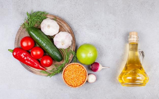Bovenaanzicht van verse groenten met linzen en olie op een grijze ondergrond.
