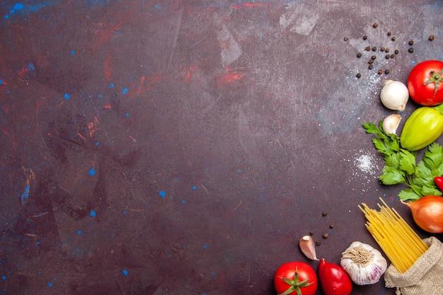 Bovenaanzicht van verse groenten met rauwe pasta op zwart