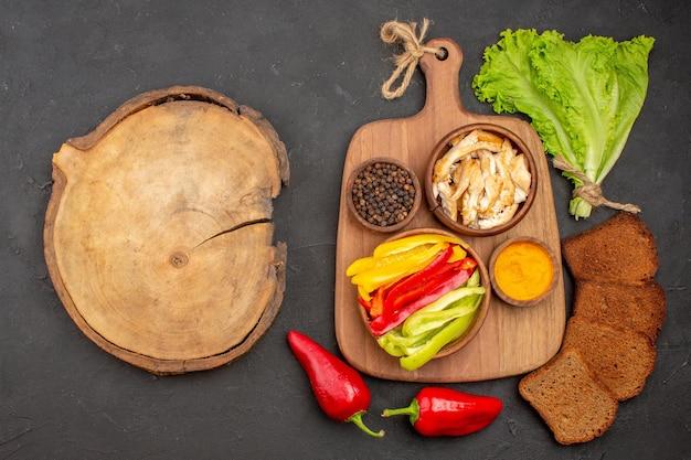 Bovenaanzicht van verse groenten met zwart brood op zwart