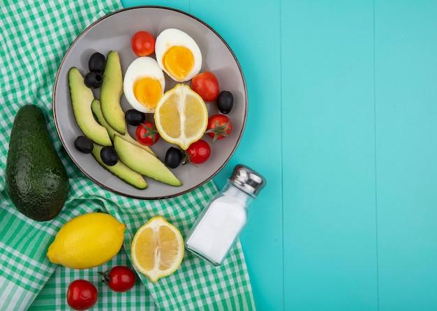 Bovenaanzicht van verse groenten op kom met avocado's citroen olijven tomaten met zoutvaatje op groen geruit tafelkleed op blauw met kopie ruimte