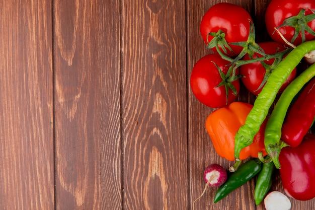 Bovenaanzicht van verse groenten, rijpe tomaten, groene chili pepers, kleurrijke paprika en radijs op houten rustieke achtergrond met kopie ruimte