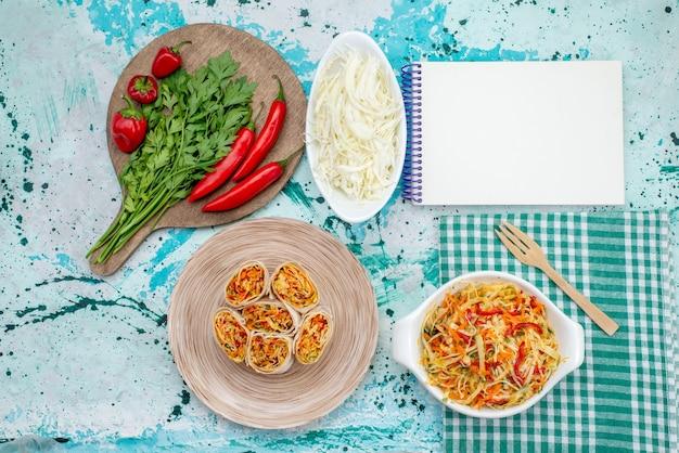Bovenaanzicht van verse groenten samen met rode pittige paprikasalade broodjes en kool op helderblauwe, plantaardige groene voedselmaaltijd