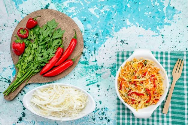 Bovenaanzicht van verse groenten samen met rode pittige paprikasalade en kool op helderblauwe, plantaardige groene voedselmaaltijd