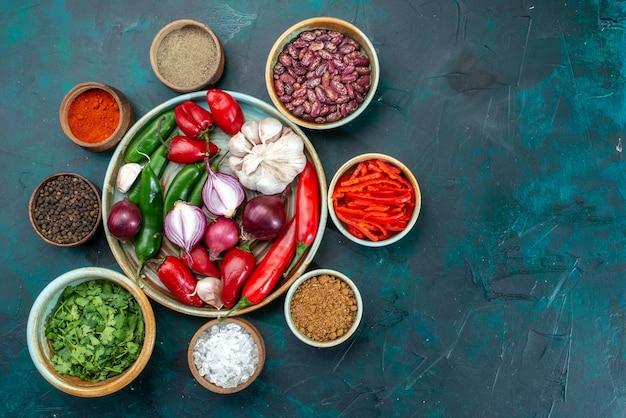 Bovenaanzicht van verse groenten, uien, knoflook, rode, kille paprika's met greens op donker, voedselingrediënt product