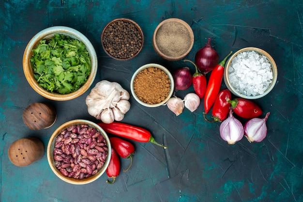 Bovenaanzicht van verse groenten, uien, paprika, knoflook, greens en kruiderijen op donkerblauw bureau, plantaardige voedselmaaltijdpeper