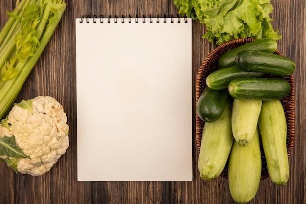 Bovenaanzicht van verse groenten zoals courgettes en komkommers op een emmer met sla, bloemkool en selderij geïsoleerd op een houten muur met kopie ruimte