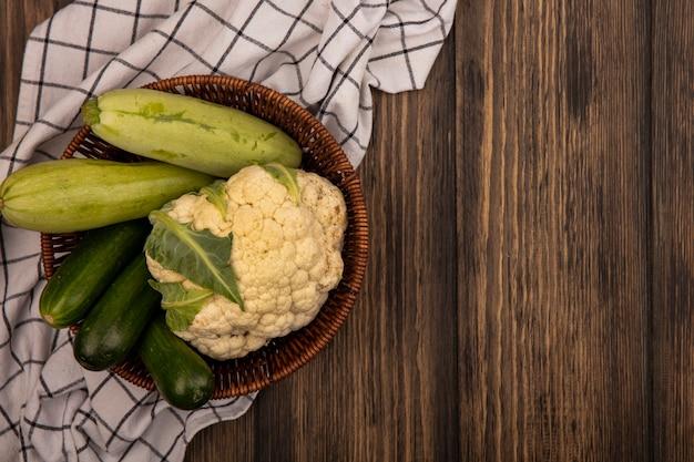 Bovenaanzicht van verse groenten zoals courgettes komkommers bloemkool op een emmer op een gecontroleerde doek op een houten muur met kopie ruimte