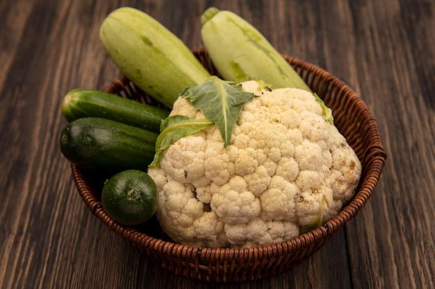 Bovenaanzicht van verse groenten zoals courgettes komkommers bloemkool op een emmer op een houten oppervlak