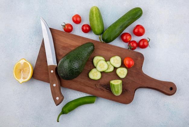 Bovenaanzicht van verse groenten zoals komkommer tomaat avocado citroen op keukenbord met mes op wit