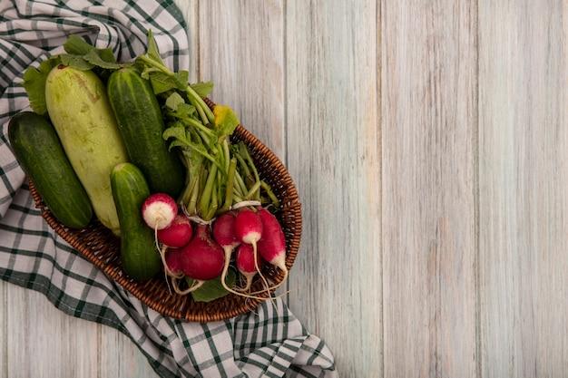 Bovenaanzicht van verse groenten zoals komkommers, courgettes en radijs op een emmer op een gecontroleerde doek op een grijze houten muur met kopie ruimte