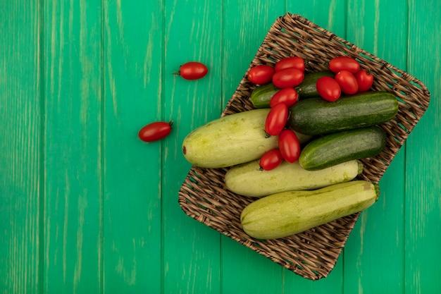 Bovenaanzicht van verse groenten zoals pruimtomaten, komkommers en courgettes op een rieten dienblad op een groene houten muur met kopie ruimte