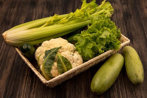 Bovenaanzicht van verse groenten zoals selderij, sla en bloemkool op een emmer met courgettes geïsoleerd op een houten achtergrond