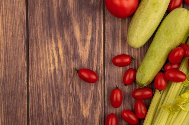 Bovenaanzicht van verse groenten zoals tomaten en courgettes geïsoleerd op een houten oppervlak met kopie ruimte