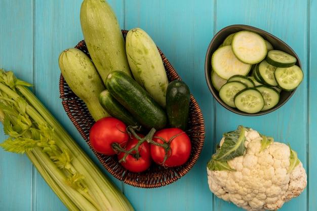 Bovenaanzicht van verse groenten zoals tomaten, komkommers en courgettes op een emmer met bloemkool en selderij geïsoleerd op een blauwe houten muur