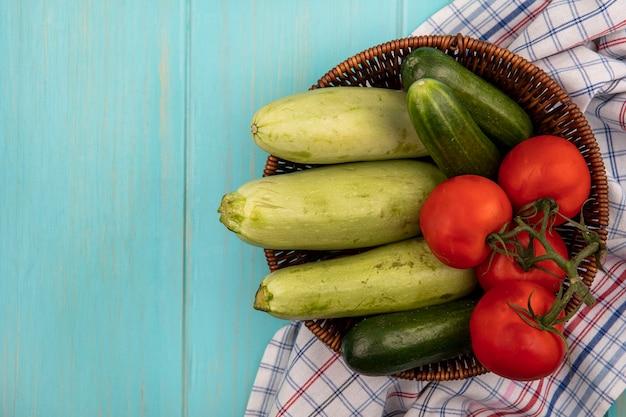 Bovenaanzicht van verse groenten zoals tomaten, komkommers en courgettes op een emmer op een gecontroleerde doek op een blauwe houten muur met kopie ruimte