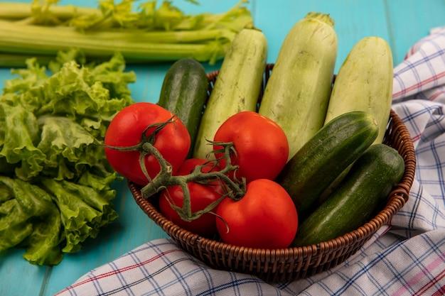 Bovenaanzicht van verse groenten zoals tomaten, komkommers en courgettes op een emmer op een geruite doek met selderij en sla geïsoleerd op een blauwe houten ondergrond