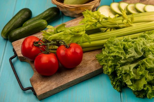 Bovenaanzicht van verse groenten zoals tomaten, selderij en courgettes geïsoleerd op een houten keukenbord met komkommers geïsoleerd op een blauwe houten achtergrond