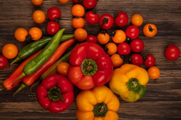 Bovenaanzicht van verse groenten zoals zachte tomaten en paprika's geïsoleerd op een houten muur