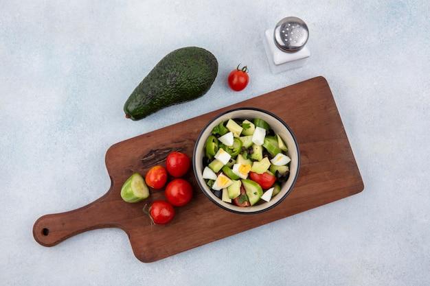 Bovenaanzicht van verse groentesalade inclusief tomaat peper komkommer in een kom op houten keukenbord met avocado en zoutvaatje op wit