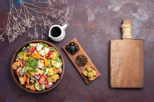 Bovenaanzicht van verse groentesalade met olijven op zwart