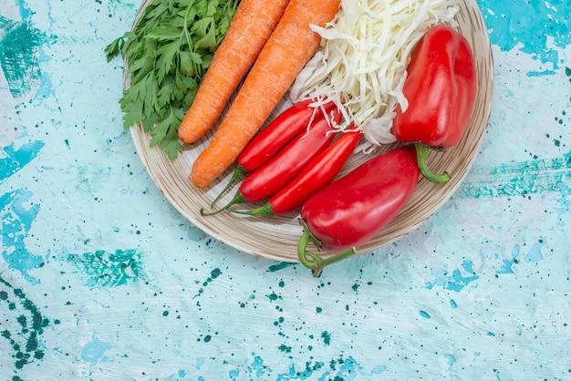 Bovenaanzicht van verse groentesamenstelling kool wortelen greens en rode pittige paprika's op helderblauw bureau, plantaardig voedsel maaltijd gezond