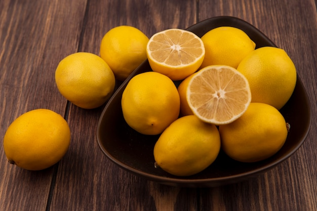 Bovenaanzicht van verse halve en hele citroenen op een kom met citroenen geïsoleerd op een houten oppervlak