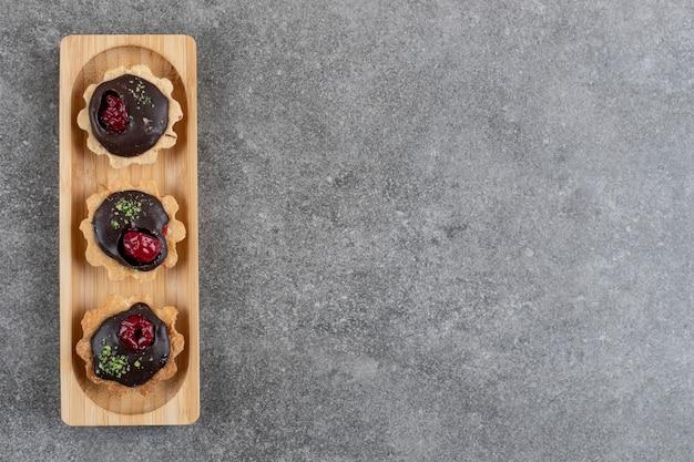 Bovenaanzicht van verse handgemaakte chocoladekoekjes op een houten bord.