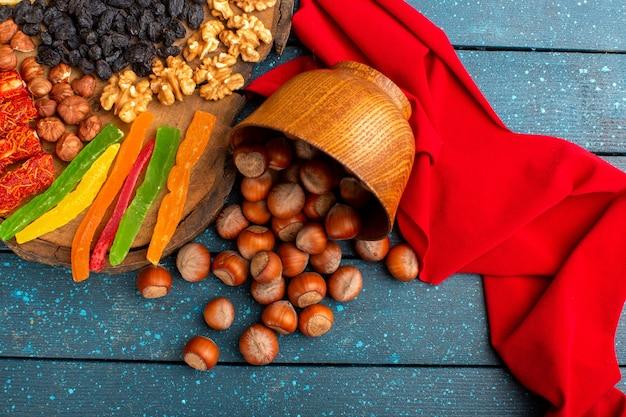 Bovenaanzicht van verse hazelnoten met walnoten en gelei op het blauwe bureau