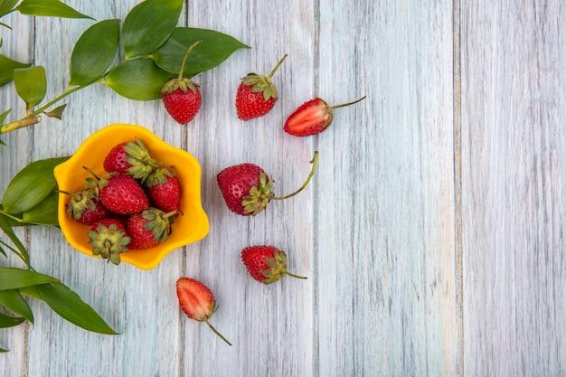 Bovenaanzicht van verse heerlijke aardbeien op een gele kom met aardbeien geïsoleerd op een grijze houten achtergrond met kopie ruimte