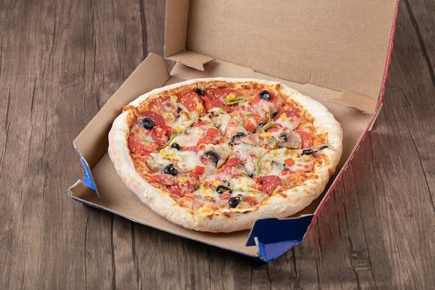 Bovenaanzicht van verse heerlijke hele pizza op pizzadoos.
