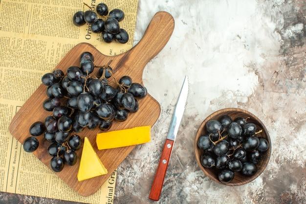 Bovenaanzicht van verse heerlijke zwarte druiventros en verschillende soorten kaas op houten snijplank