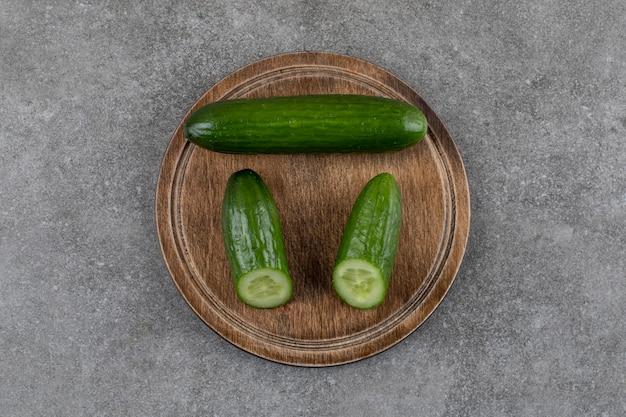 Bovenaanzicht van verse hele of half gesneden komkommers op een houten bord.