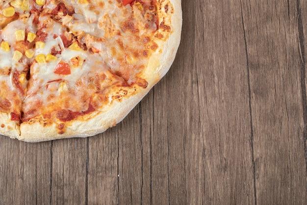 Bovenaanzicht van verse hete mozzarella pizza op houten tafel.