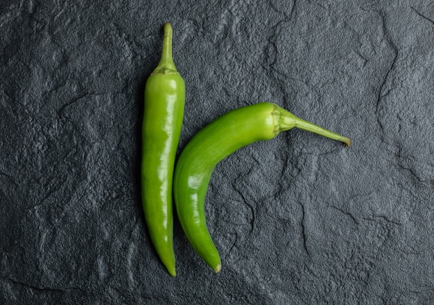 Bovenaanzicht van verse hete pepers op zwarte achtergrond. Gratis Foto
