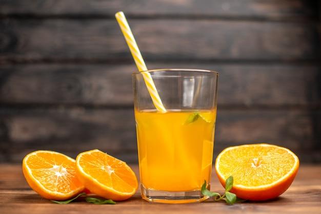 Bovenaanzicht van verse jus d'orange in een glas geserveerd met tube mint en sinaasappellimoenen op een houten tafel