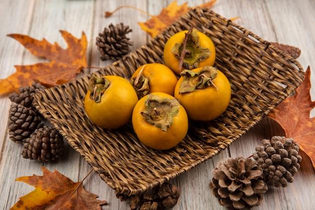 Bovenaanzicht van verse kaki fruit op een rieten dienblad met bladeren op een grijze houten tafel