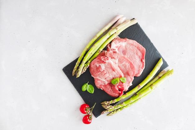 Bovenaanzicht van verse karbonades steaks op een steen zwart bord met verse groene asperges en cherrytomaatjes.