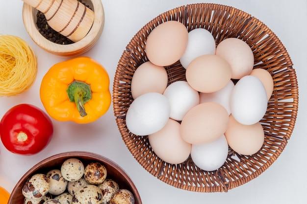 Bovenaanzicht van verse kippeneieren op een emmer met een tomaat een peper op witte achtergrond