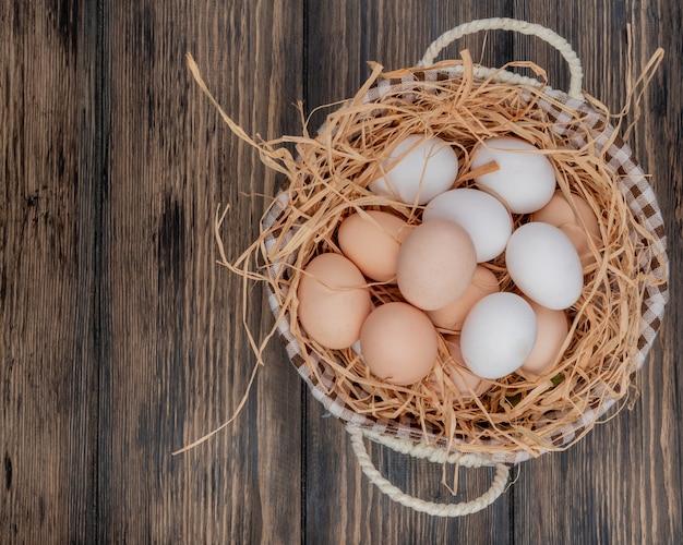 Bovenaanzicht van verse kippeneieren op nest op een emmer op een houten achtergrond met kopie ruimte