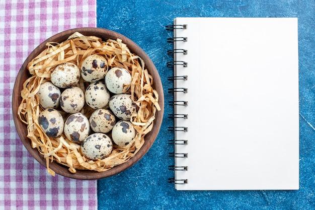 Bovenaanzicht van verse kippeneieren van pluimvee in een weefselmand in een bruine kom op een paarse gestripte handdoek en een spiraalvormig notitieboekje op blauwe achtergrond