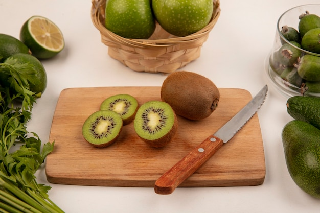 Bovenaanzicht van verse kiwi's op een keukenbord met mes met appels op een emmer met feijoas op een glazen kom met limoenen en avocado's geïsoleerd op een witte muur