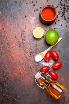 Bovenaanzicht van verse kleine tomaten met olie op donkere ondergrond
